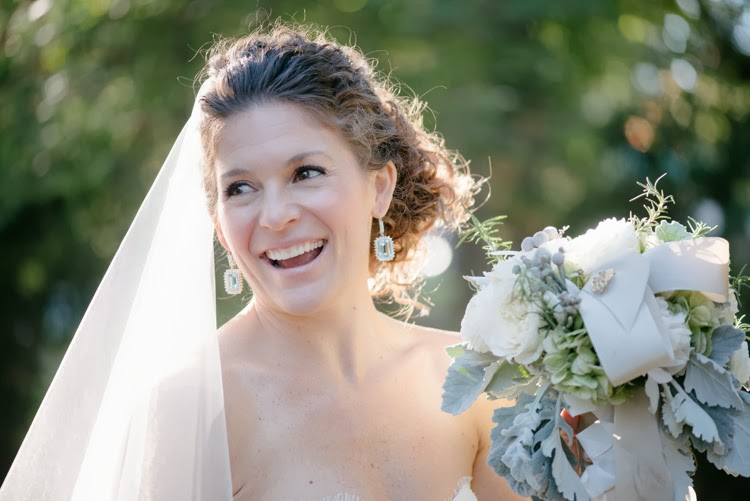 bride in her Monique Lhuillier wedding dress with her bouquet of flowers and sunshine back lighting her