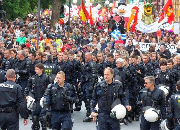 35 moments of violence that brought out incredible human compassion - german riot officers take off their helmets and escort occupy protesters