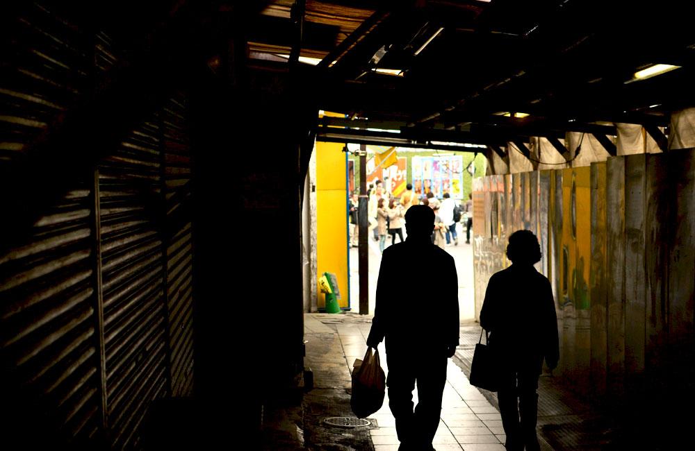下北沢駅のアーケードでスーパーの袋を持って歩く老夫婦の写真