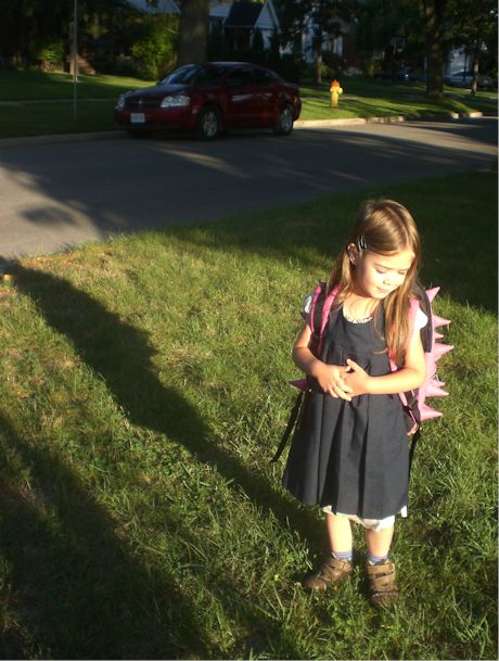 Anxious but happy as she waits for the school bus.