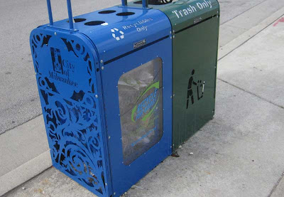 Side of the blue recycling container with scroll-work cutaways