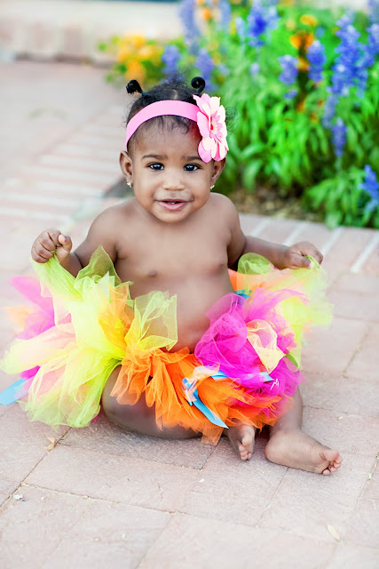 Adorable little girl wearing a bright colored tutu stairs into camera