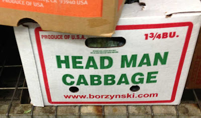 Produce box with green plain letters on the side that say HEAD MAN CABBAGE