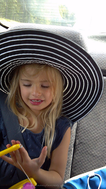 Little girl in her grandmother's big hat.
