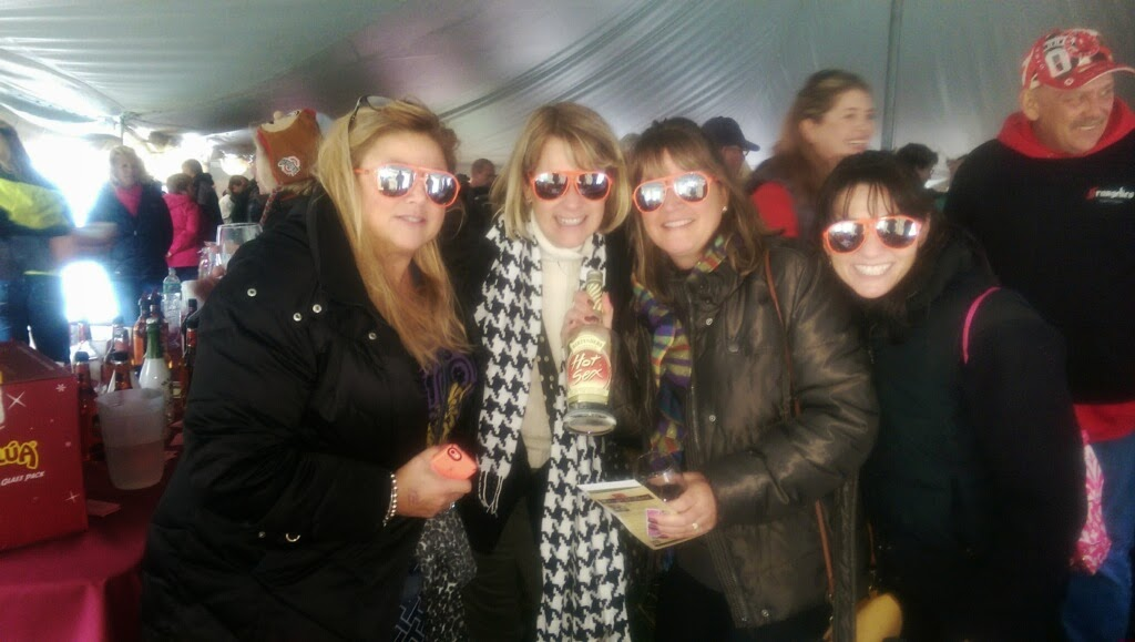 "group of women wearing orange sunglasses with bottle of ""Hot Sex"" liqueur"