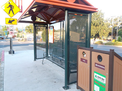 Bus shelter with waste container next to it