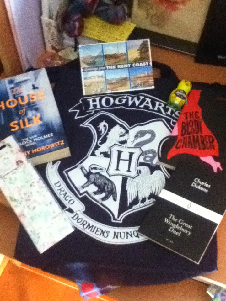 "Postcard from Kent, The House of Silk by Anthony Horowitz, The Bloody Chamber by Angela Carter, The Great Winglebury Duel by Charles Darwin, Harry Potter tote bag, book mark with flowers on, smarties, badge saying ""Read Local"""