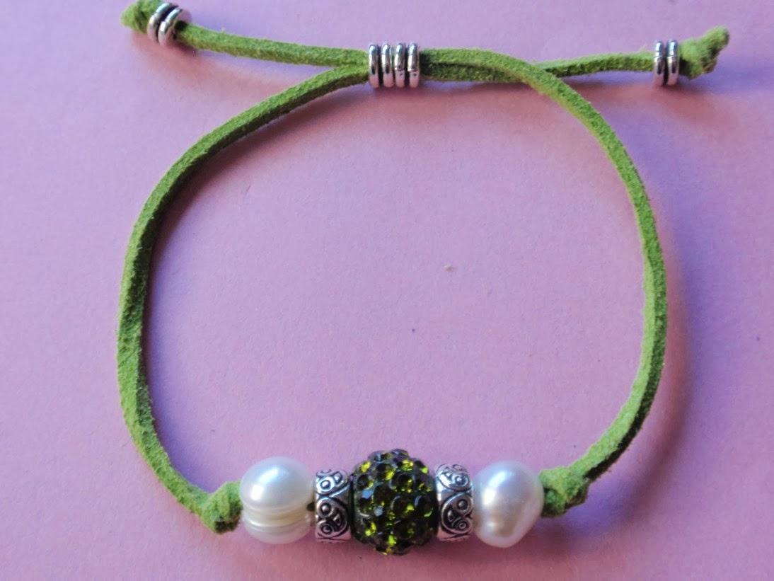 Pulsera ajustable en antelina color verde con cristal en tonos plateados en el centro y perlas de agua dulce a los lados.