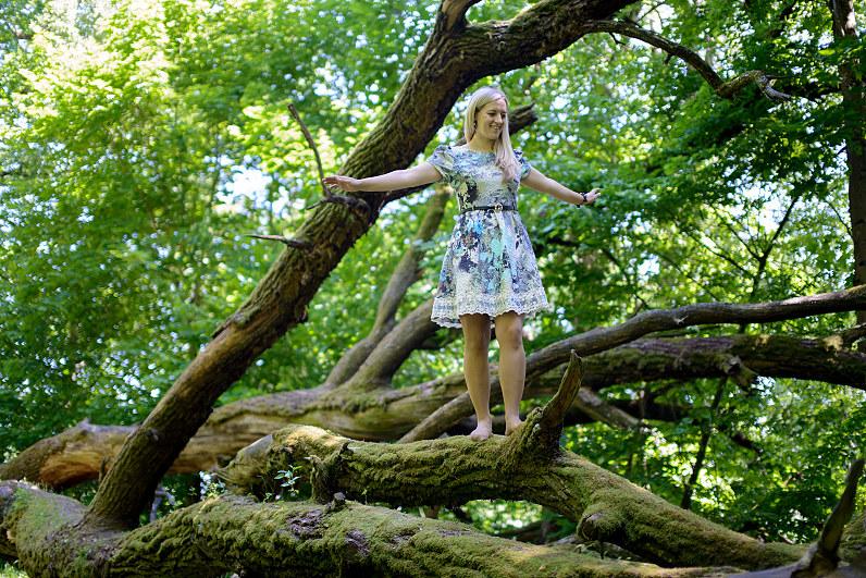 mergina prie didelio nuvirtusio medžio