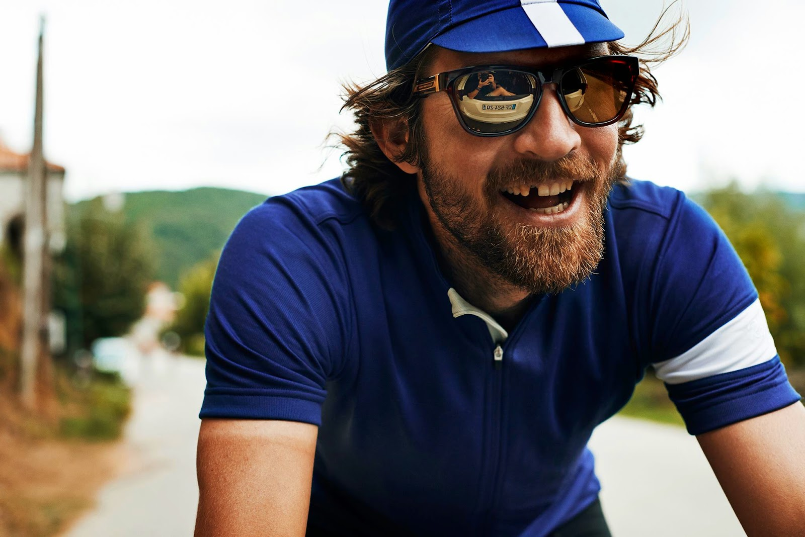 Photograph of a smiling cyclist, with one tooth missing.
