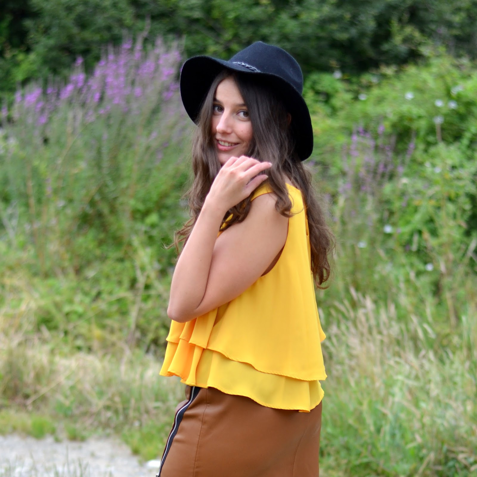 leatherette brown skirt, mustard top, black hat