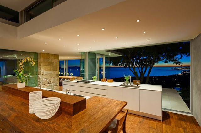 Panoramic Night View near Modern Home Kitchen with White Counter and Wooden Stools