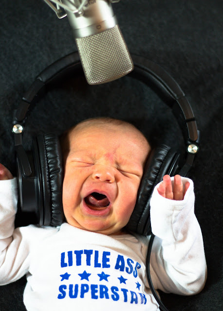 Newborn baby with headphones screaming into a microphone.