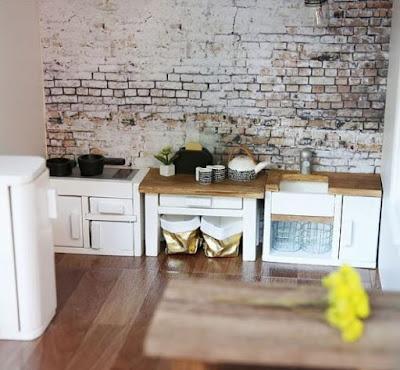 Modern dolls' house miniature industrial-style kitchen, with exposed brick wall and Marimekko Siirtolapuutarha mugs and teapot.