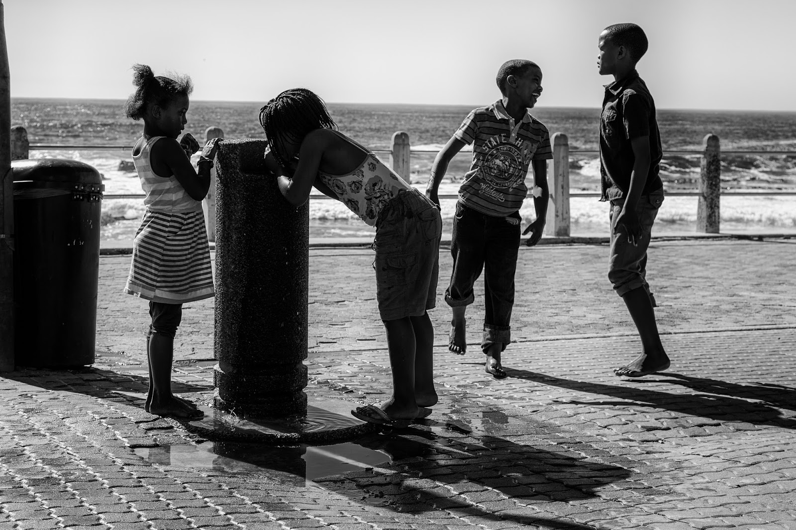 Four children around a drinking fountain