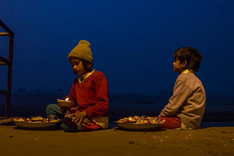 Brother and Sister selling Diyas decorated with flowers and waiting for customers to offer to Yamuna River at Vrindavan as part of prayer.