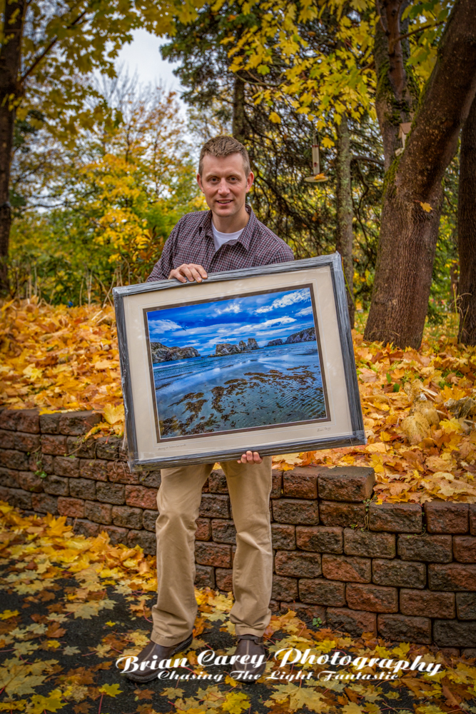 "Dr Chris Patey holding a print of ""Morning at Salmon Cove Sands"". One of six images in the collection."