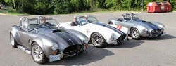 Classic silver Shelby and a classic white Shelby. Racing strips and a sunny day.