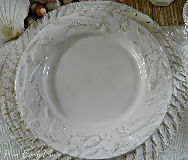 White fish embossed dinner plate with white washed charger plate