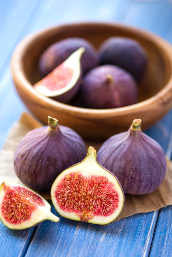 fresh black figs in a bowl on a blue table