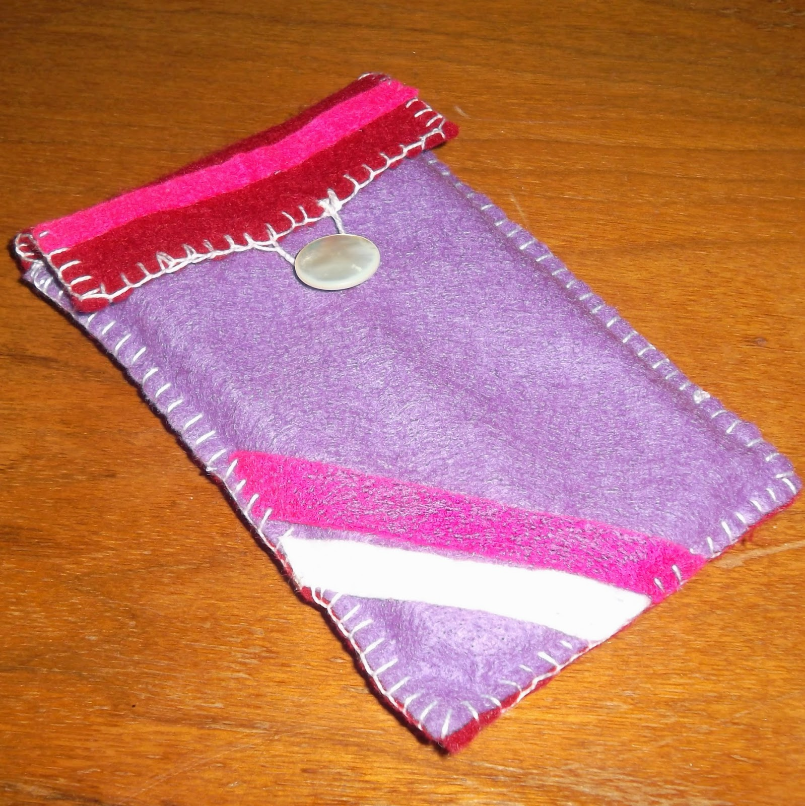 Purple felt pouch with a deep-burgundy flap folded over the top and secured with a white button. The pouch is stitched at bottom and sides with a blanket stitching, which also outlines the edge of the flap and forms a loop for the button closure. The pouch is decorated with two diagonal stripes, in shades of pale and hot pink in the lower left corner of the pouch and with a hot pink stripe across the flap.
