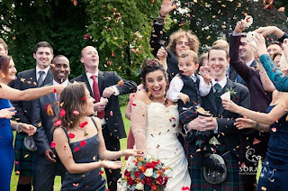 bride and groom with bridal party throwing confetti