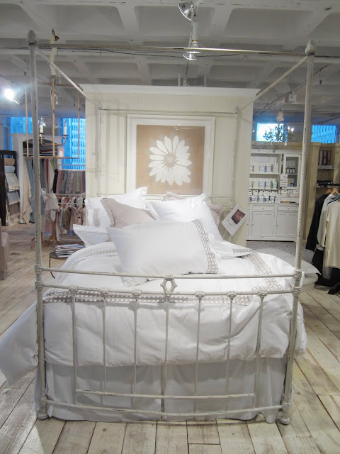 White bedding with cane pattern board by Monde Maison on a bed with a metal bedframe