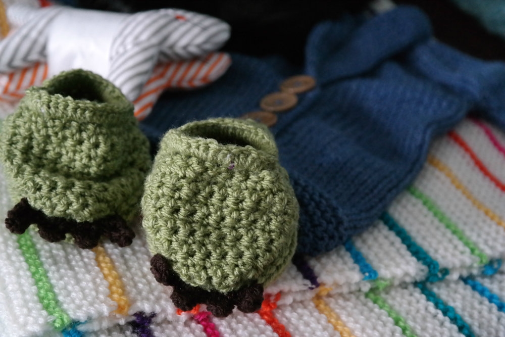 Handmade knitted baby gifts: dinosaur feet booties; cardigan; stripy blanket. Also cat rattles from Ikea.