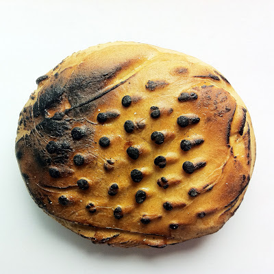 A piece of bread which has been pressed through a grater and then the raised sections burnt.