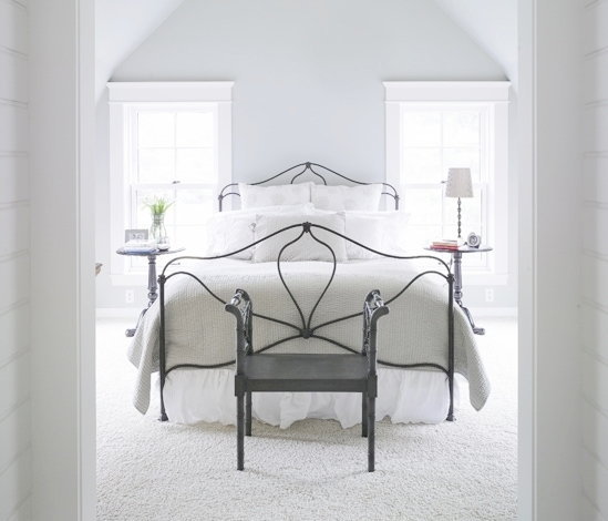 bedroom with iron bedframe and white bedding, vaulted ceiling, foot bench and two circle night stands one with a reading lamp the other with a  vase of flowers