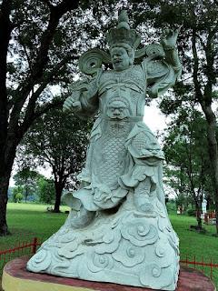 Estátua de guerreiro pronto para arremessar pedra com a mão esquerda.