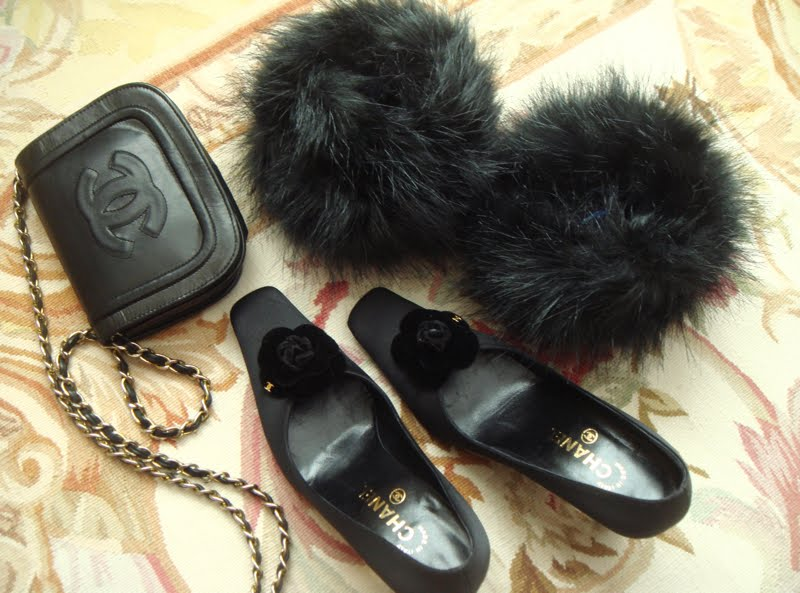 Close up of shoes, fur cuffs, and crossbody bag on floor.