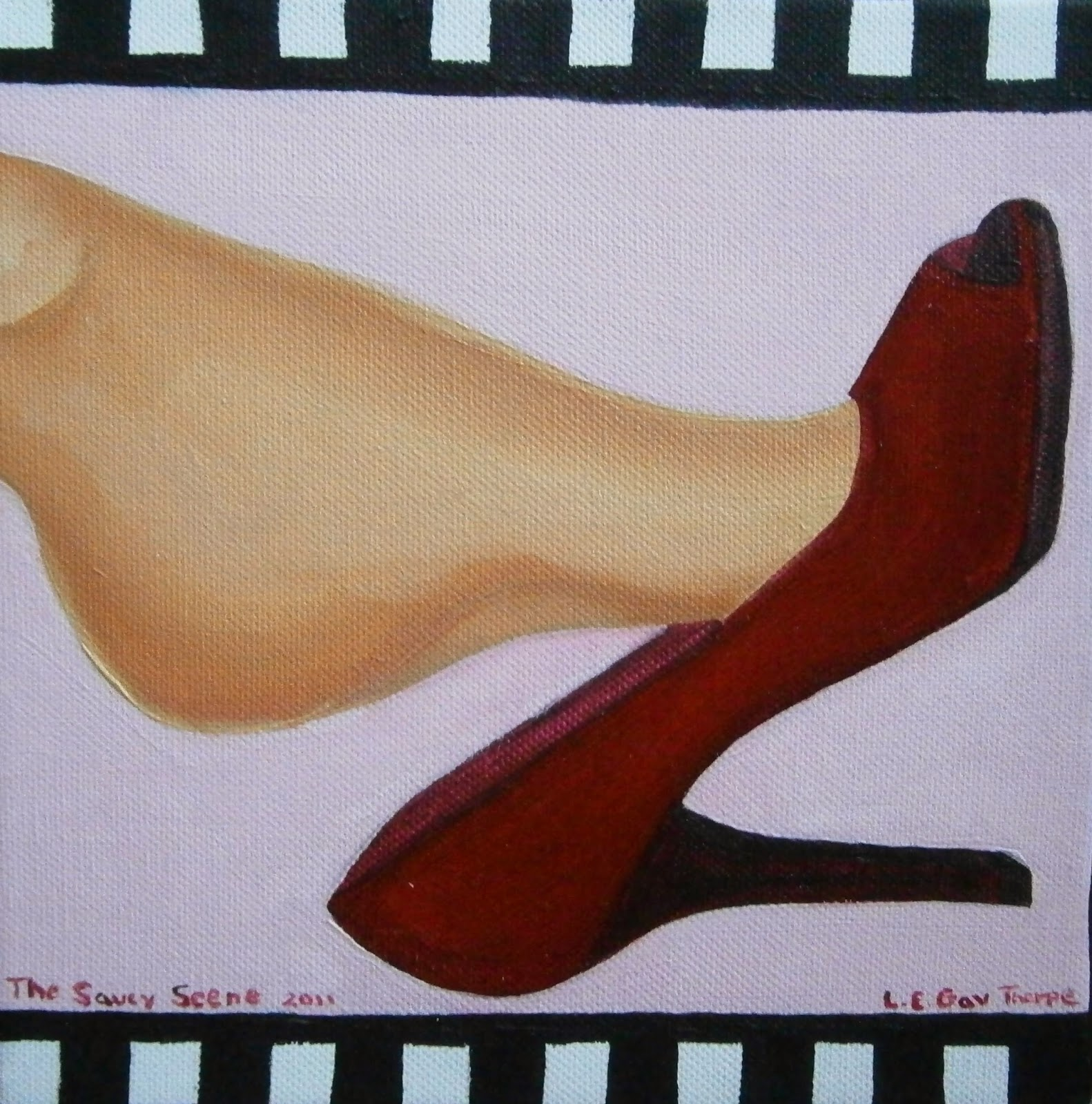 A woman dangling a red high heel off of her foot