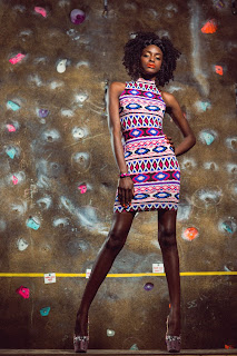 Girl wearing an aztec print dress and Louboutin shoes poses with afro style hair with braid and orange lipstick