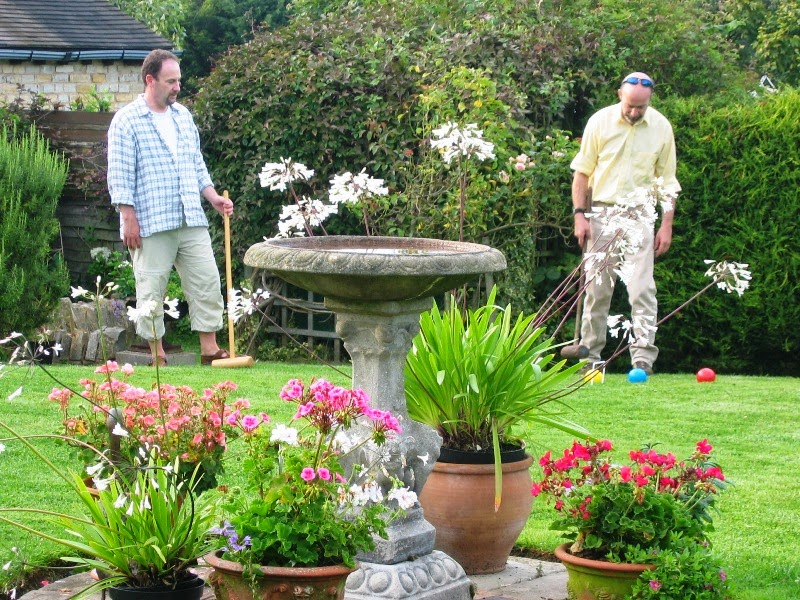 Two croquet players and a garden urn with flowers