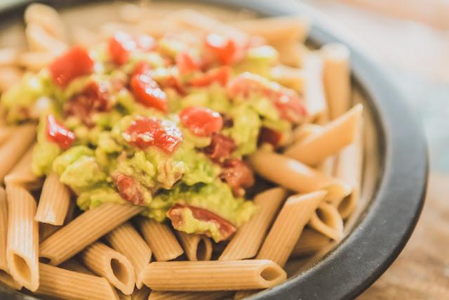 Teller Vollkornpasta mit Avocado und Tomaten vegan
