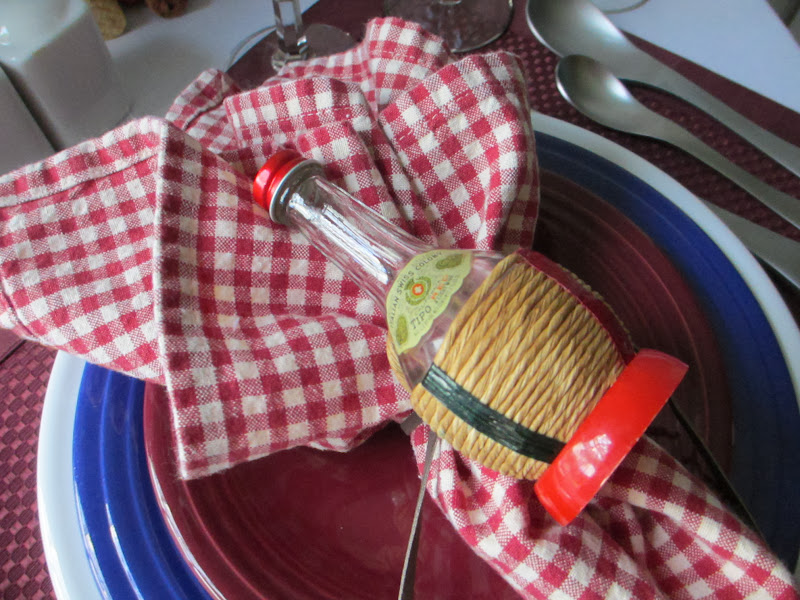The napkin ring is a small Italian style wine bottle and leather title=