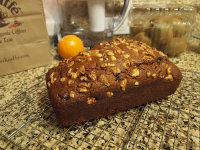 a loaf of banana bread topped with walnut pieces and a few blueberries visible on the top