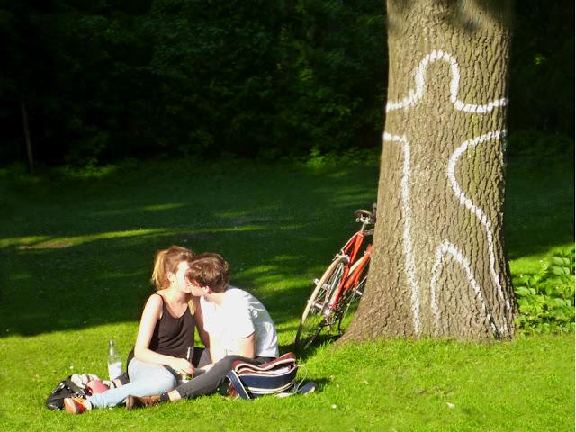 Ein Liebespärchen sitzt auf einer Wiese, hinter ihnen ein Baumstamm, auf den mit weißer Farbe der Umriss eines Menschen gemalt wurde.