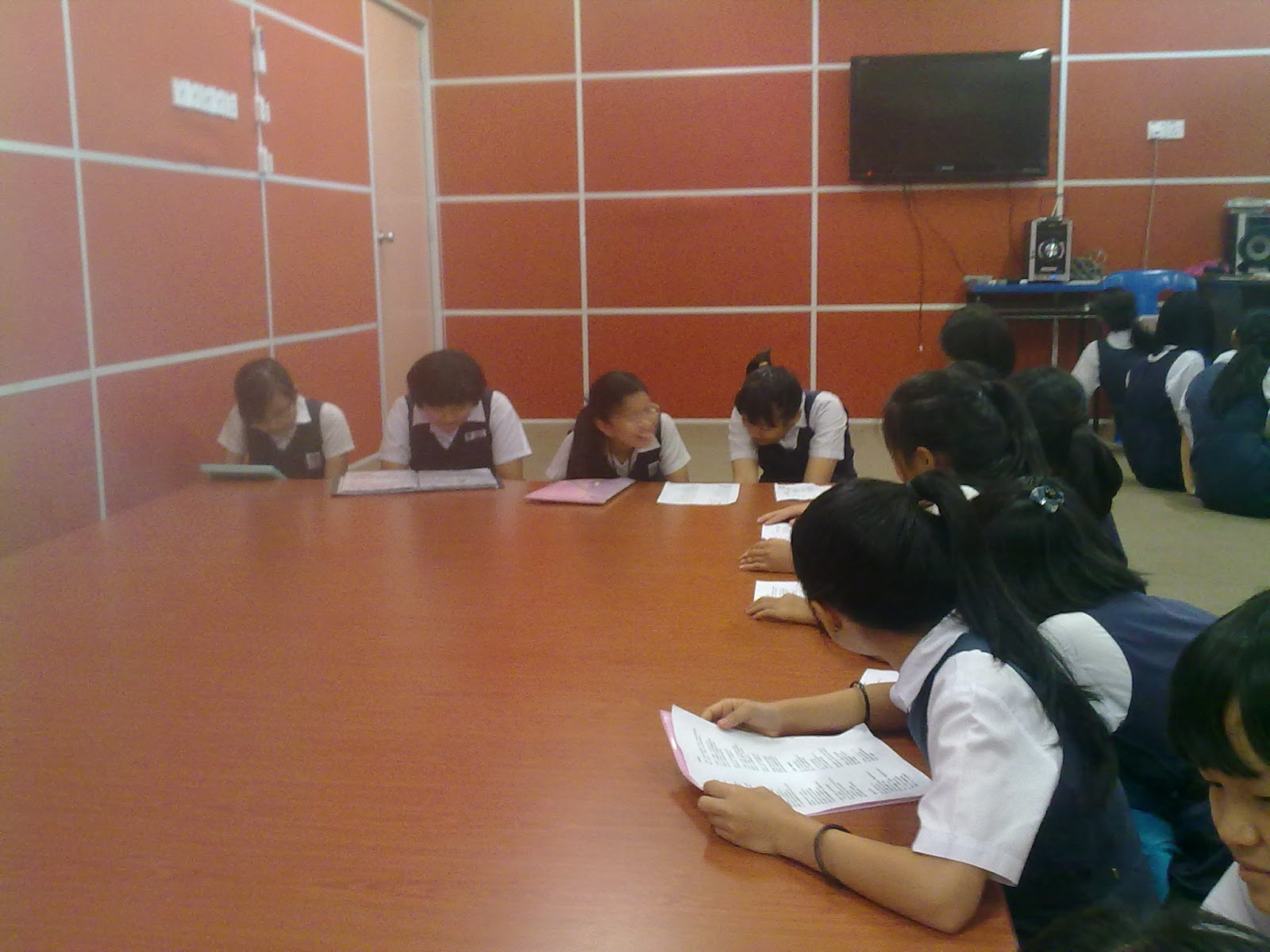 Murid-murid menyanyi sambil melihat lirik lagu.