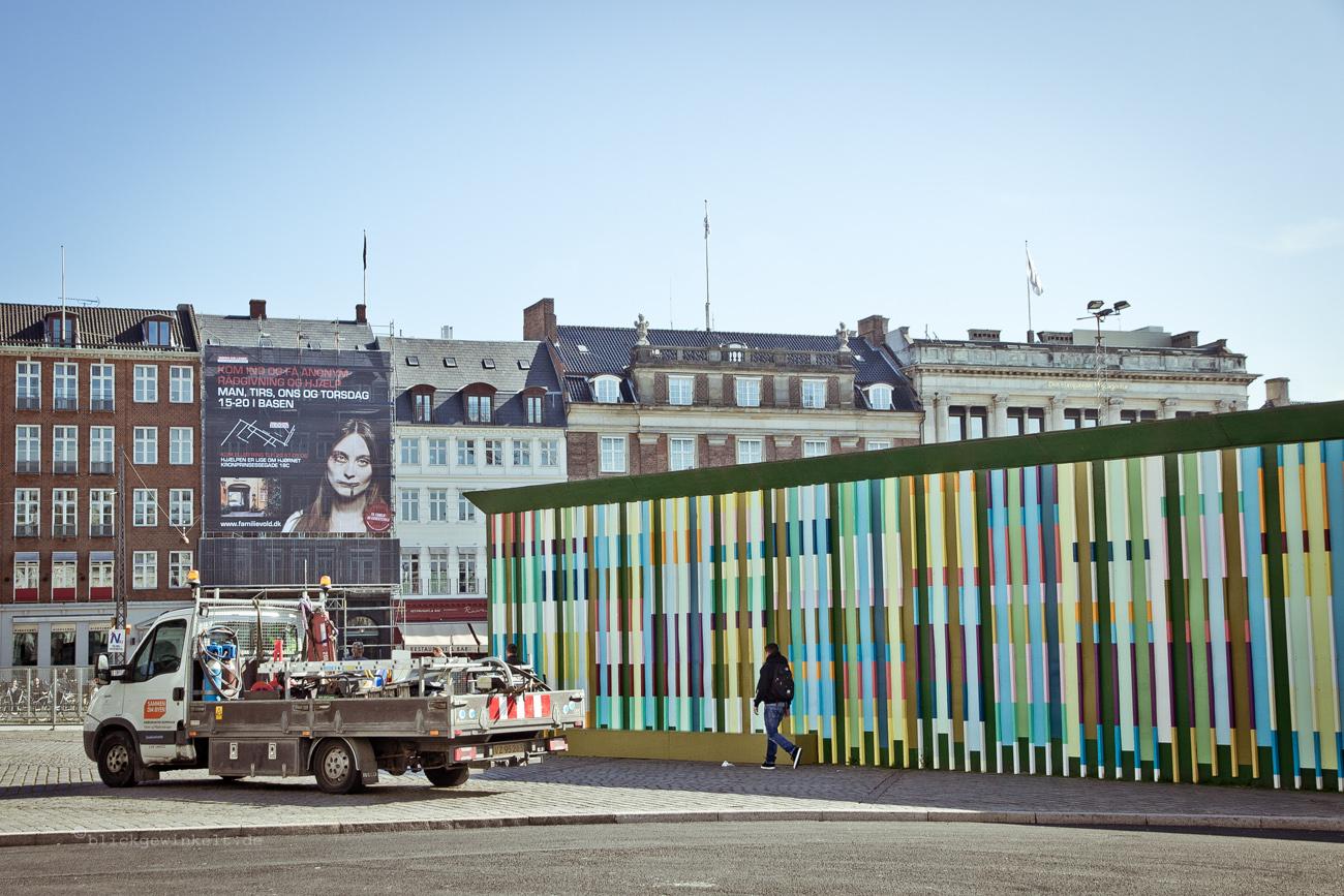 Bauzaun und Werbeposter an Häuserfassade