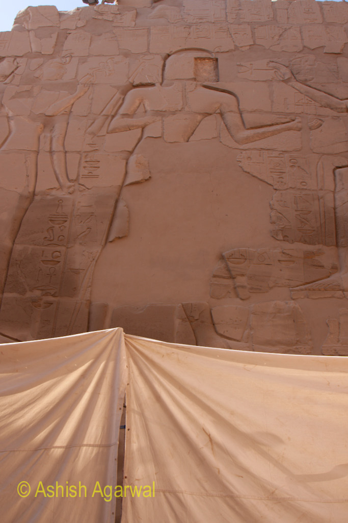 Carving on the pylon of the Karnak temple with some tents at the bottom