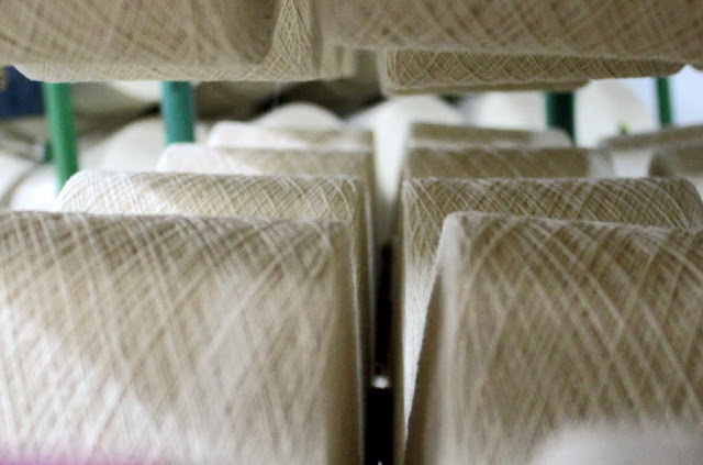 spools of white thread in a cotton mill
