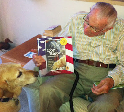 John Neff holds up the book Dog Heroes as Bonnie looks on.