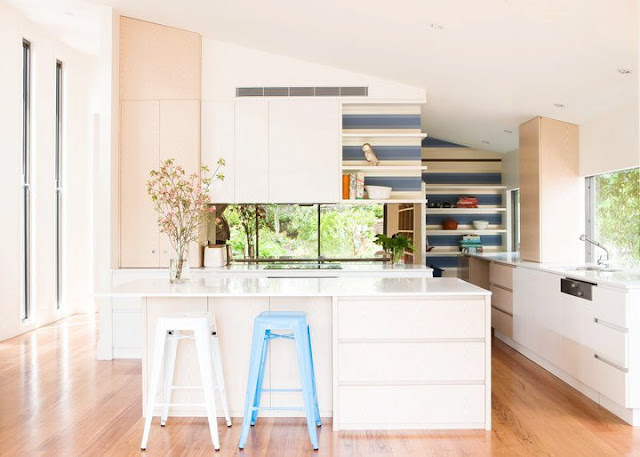 kitchen with blue and white backsplash, white island, wood floors and white counters and cabinets with a lot of natural light