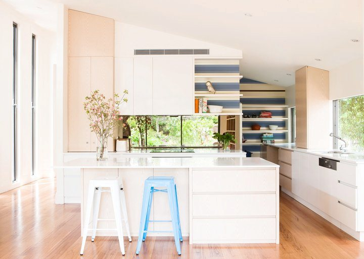 kitchen with blue and white backsplash, white island, wood floors and