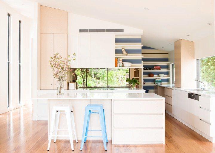kitchen with blue and white backsplash, white island, wood floors and