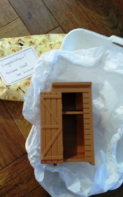 An unwrapped gift containing a dolls' house miniature shed.