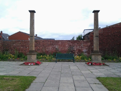 Two isolated pillars set on blocks of stone inscribed with names. Between the two is a bench.  The whole set in a paved and bordered garden with a high wall at the back.