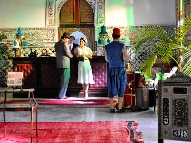 Sira Quiroga blusa y falda blanca con lunares y detalles en rojo. Llegada al hotel Tánger. El tiempo entre costuras. Capítulo 1.